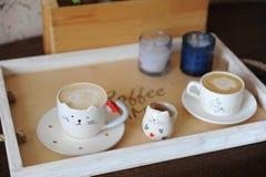 Cappuccino de café dans la tasse mignonne sous forme de chat Sur un plateau en bois Bougies sur le fond Photographie stock libre de droits