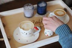 Cappuccino de café dans la tasse mignonne sous forme de chat Sur un plateau en bois Bougies sur le fond Photographie stock