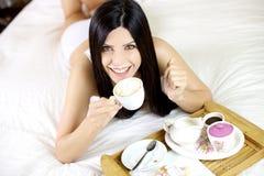 Cappuccino de consumición de la mujer hermosa en cama Imagen de archivo libre de regalías