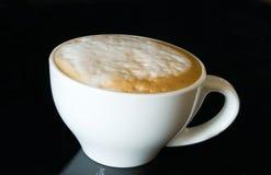 Cappuccino de la taza en el negro Fotos de archivo libres de regalías