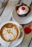 Cappuccino della tazza di caffè con i bigné fotografie stock