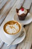 Cappuccino della tazza di caffè con i bigné immagini stock libere da diritti