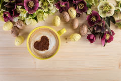Cappuccino do copo de café com a decoração da Páscoa na tabela de madeira clara Espuma da forma do coração, vista superior Fotos de Stock