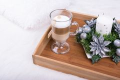 A cappuccino drink and Christmas decoration with candle, fir branch and silver balls on white furry carpet Stock Images