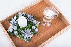 A cappuccino drink and Christmas decoration with candle, fir branch and silver balls on white furry carpet Stock Image