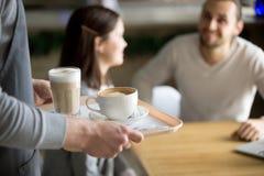 Cappuccino e latte do serviço da empregada de mesa a acoplar-se no café, close up Fotos de Stock Royalty Free