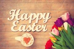 Cappuccino e parole Pasqua felice vicino ai fiori Immagine Stock