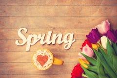 Cappuccino e primavera di parola vicino ai fiori Immagine Stock