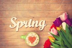 Cappuccino e primavera di parola vicino ai fiori Fotografia Stock