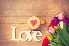 Cappuccino ed amore di parola vicino ai fiori Fotografia Stock Libera da Diritti