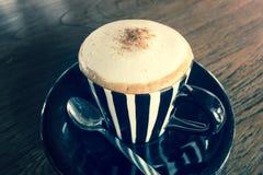 Cappuccino in een kop op een houten lijst - uitstekend effect Stock Foto