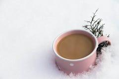 cappuccino em um copo cor-de-rosa na neve Fotografia de Stock Royalty Free