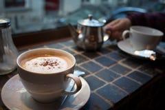 Cappuccino en thee stock afbeeldingen