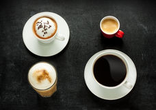 Cappuccino, espresso, americano and latte coffee on black Stock Images