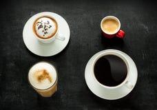 Cappuccino-, espresso-, americano- och lattekaffe på svart Arkivbilder
