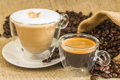 Cappuccino and espresso in glassy cups with roasted coffee beans Royalty Free Stock Photo