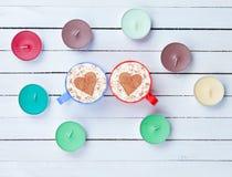 Cappuccino et bougies sur le fond blanc Photographie stock libre de droits