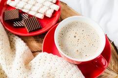Cappuccino et chocolat sur un lit avec le plaid Photographie stock
