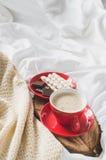 Cappuccino et chocolat sur un lit avec le plaid Photo libre de droits