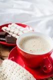 Cappuccino et chocolat sur un lit avec le plaid Image stock