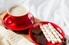 Cappuccino et chocolat sur un lit avec le plaid Images libres de droits