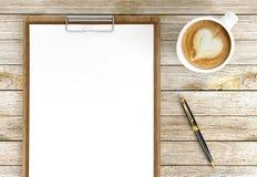 Cappuccino filiżanka z pustymi papierami na piórze, kawie i biznesu tle schowka i ballpoint, obrazy stock