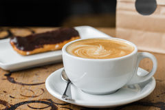 Cappuccino flatwhite coffee with eclair stock photos
