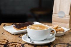 Cappuccino flatwhite koffie met eclair Stock Afbeeldingen