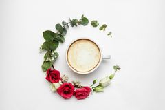 Cappuccino and flowers composition. White coffee cup with creamy foam, fresh flowers circle at white, top view. Hot royalty free stock image