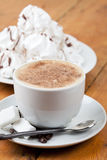 Cappuccino with foam and meringues on white plate Stock Image