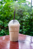 Cappuccino frappe in coffee shop garden. Cappuccino frappe or flappucino on wood table in coffee shop garden stock photography