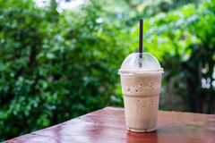 Cappuccino frappe in coffee shop garden. Cappuccino frappe or flappucino on wood table in coffee shop garden royalty free stock images