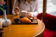 Cappuccino and frensh croissant in the cafe. A woman eats her breakfast. Wooden background. royalty free stock images