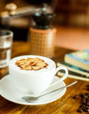 Cappuccino with fresh coffee beans, water and books on a brown b Royalty Free Stock Photo