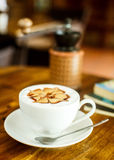 Cappuccino with fresh coffee beans, water and books on a brown b Stock Photo