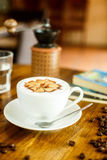 Cappuccino with fresh coffee beans, water and books on a brown b Stock Photos