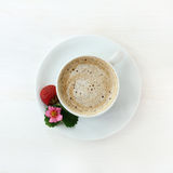 Cappuccino garnished with strawberries. Frothy coffee with decoration of fruit, flower and leaf strawberries on a light wooden background top view Stock Photos