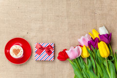 Cappuccino and gift box near flowers Royalty Free Stock Images