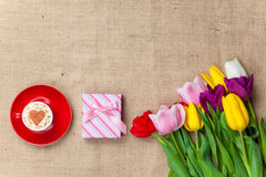 Cappuccino and gift box near flowers Stock Photos