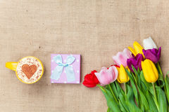 Cappuccino and gift box near flowers Stock Photo