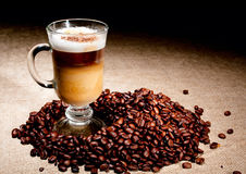Cappuccino glass with coffee beans Royalty Free Stock Photos