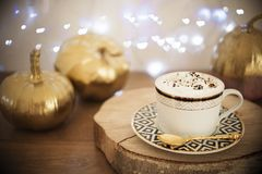 Cappuccino and gold pumpkins. Stripe design, heart lights bokeh Royalty Free Stock Photo
