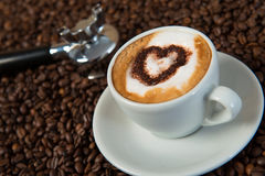 Cappuccino with heart. On coffee beans Stock Photography