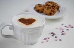 Cappuccino with heart pattern of cinnamon and cookies Royalty Free Stock Photo