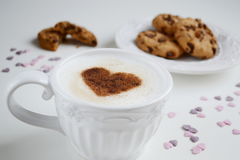Cappuccino with heart pattern of cinnamon and cookies Royalty Free Stock Images