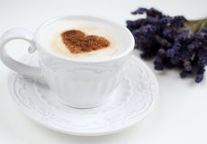 Cappuccino with heart pattern of cinnamon and flowers composition Stock Image