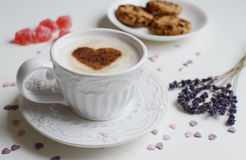 Cappuccino with heart pattern of cinnamon and flowers composition Royalty Free Stock Photos