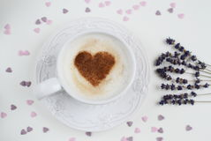 Cappuccino with heart pattern of cinnamon and flowers composition Stock Photos