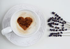 Cappuccino with heart pattern of cinnamon and flowers composition Royalty Free Stock Photo
