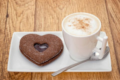 Cappuccino with a heart shaped cookie biscuit Stock Photos